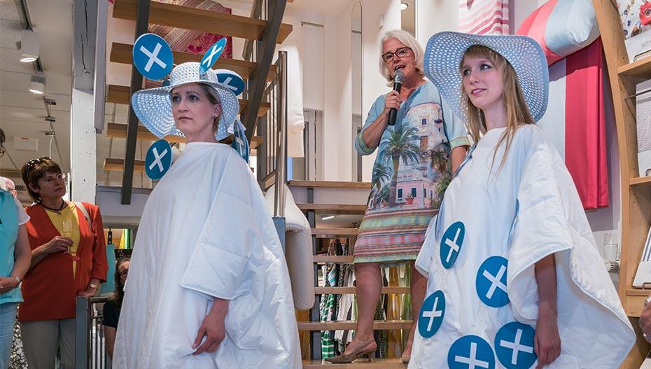 Susanne Heller moderiert Modenschau mit zwei Frauen in Bettwäsche